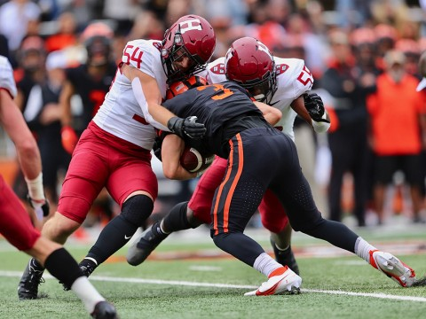 Two Harvard linebackers tackle a Princeton receiver