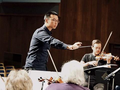 Sam Wu conducts an orchestra