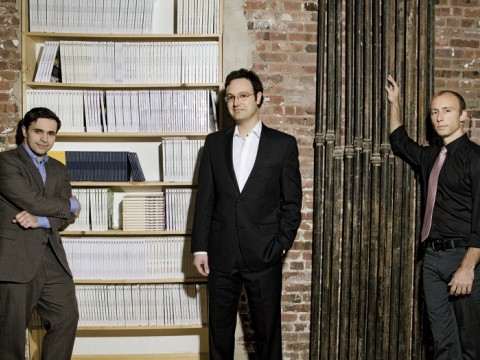 Editors with their product. Left to right, Keith Gessen, Mark Greif, and Chad Harbach of <i>n+1</i> at their Brooklyn office, with a bookcase full of past issues.
