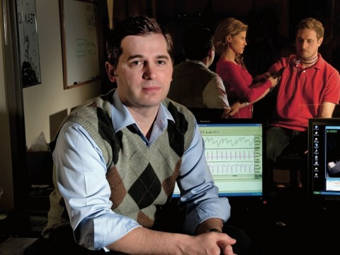 Matthew Nock sits in his lab's control room, where researchers record subjects' behavioral and physiological responses during experiments. For example, they might measure whether people who engage in self-injury show greater emotional distress, in response to frustrating tasks, than people who do not. (Nock's lab manager and a postdoctoral fellow are seen in the adjoining room through one-way glass.)